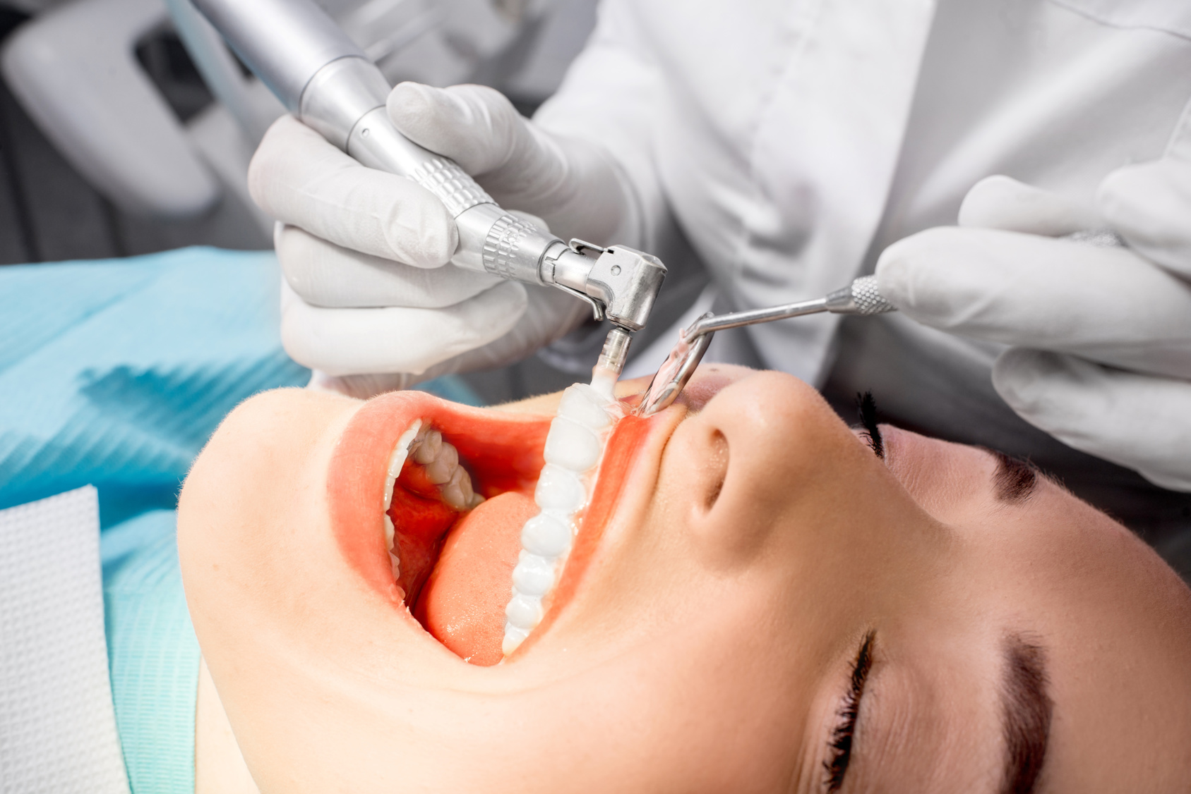 Dentist making professional teeth cleaning female young patient at the dental office. Close-up plan